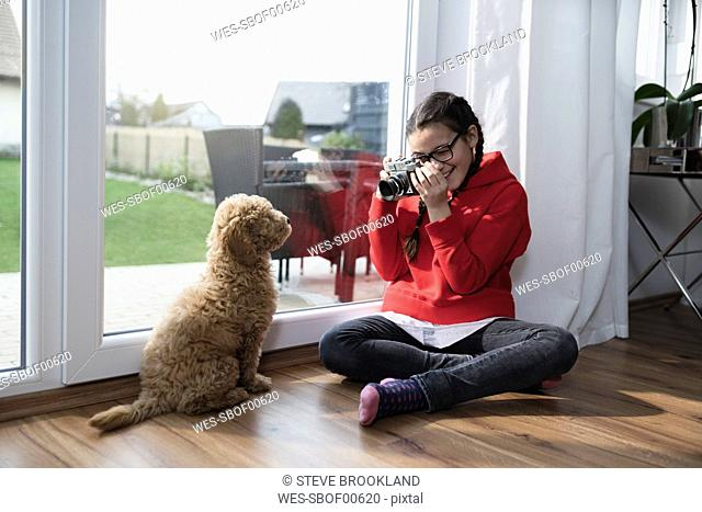 Girl taking a picture of her dog in living room