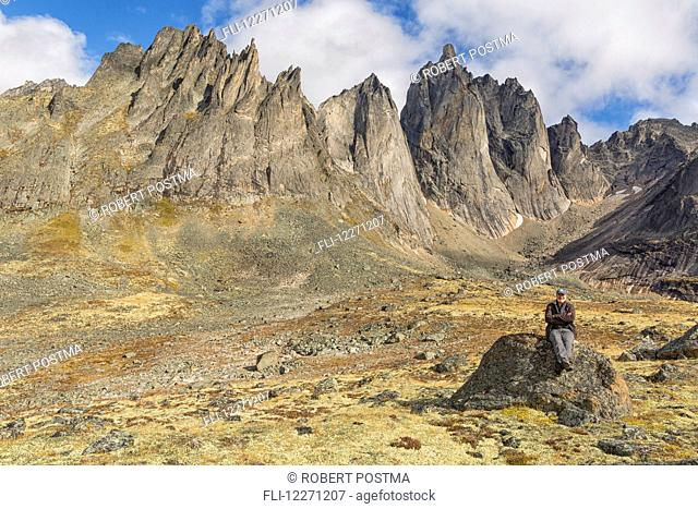 Man sitting on a rock underneath the jagged granite peaks of Tombstone Territorial Park; Yukon, Canada