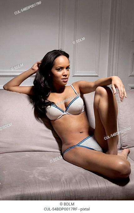Woman in lingerie sitting on sofa
