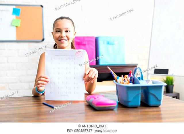 Smiling school girl showing perfect test result at table in house