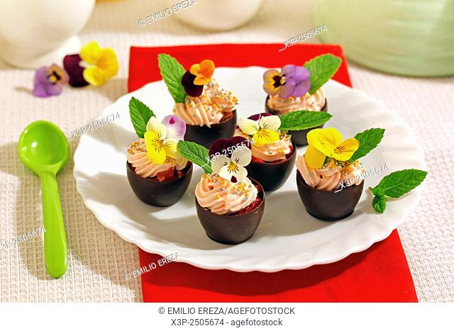 Chocolate cups with cream and flowers