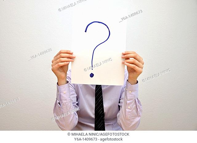 Businesswoman holding card with question mark in front of face