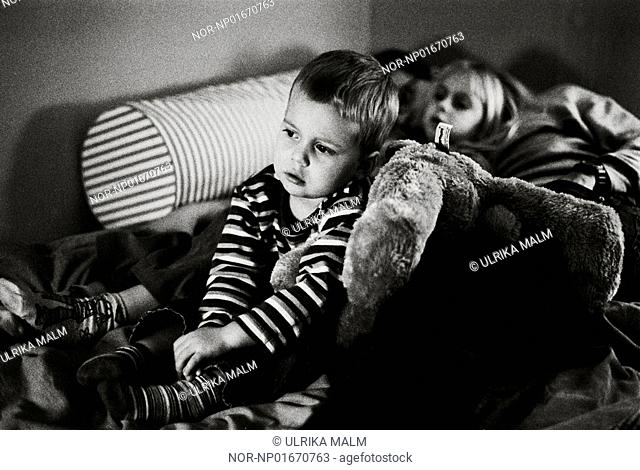 Close-up of a boy watching television with sister