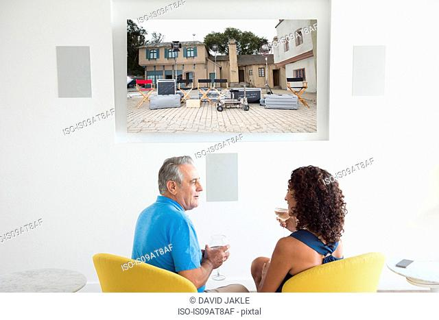 Senior man and wife watching photographs on digital screen