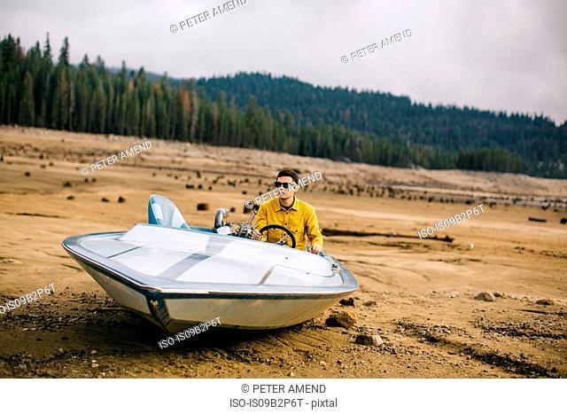 Young man sitting in beached speedboat, Huntington Lake, California, USA