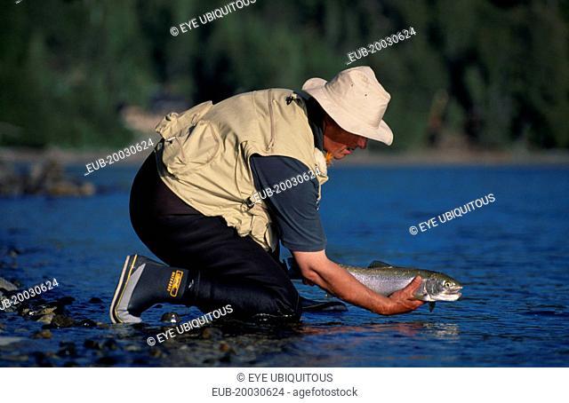 Parque Nacional Nahuel Huapi, Lago Nahuel Huapi. Fly fisherman releasing fish