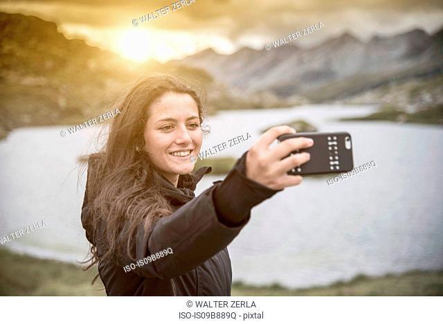 Teenage girl taking selfie in front of lake smiling, San Bernardino, Ticino, Switzerland, Europe