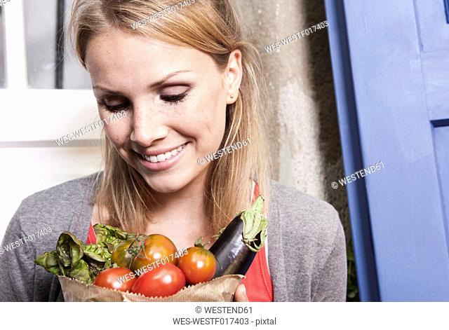 Italy, Tuscany, Magliano, Close up of young woman holding bag of vegetables, smiling