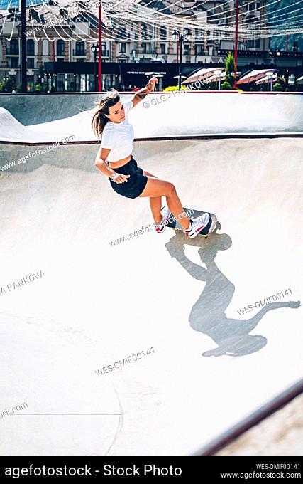 Young woman practicing skateboarding at skateboard park