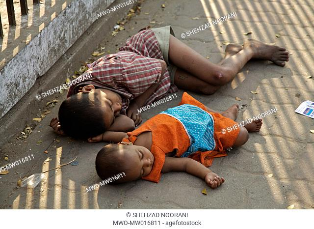 Children sleeping on the footpath, outside a park Although one of the busiest street in farm gate area, a major transit point in Dhaka city