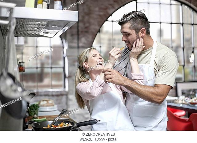 Couple cooking together and having fun in kitchen