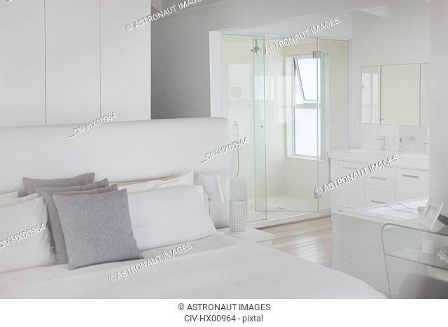 White bedroom and en suite bathroom in home showcase interior