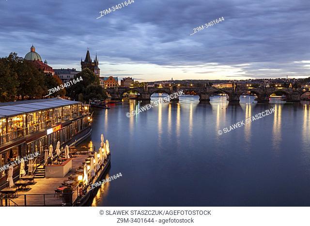 Evening on Vltava river in Prague, Czechia. Charles Bridge in the distance