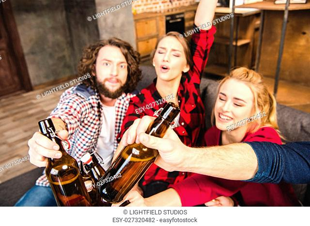 Smiling friends holding beer bottles while sitting on sofa