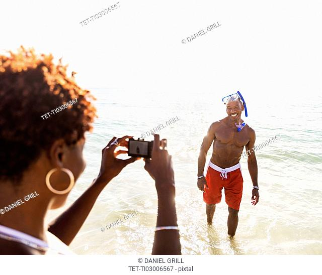 Woman photographing man on beach