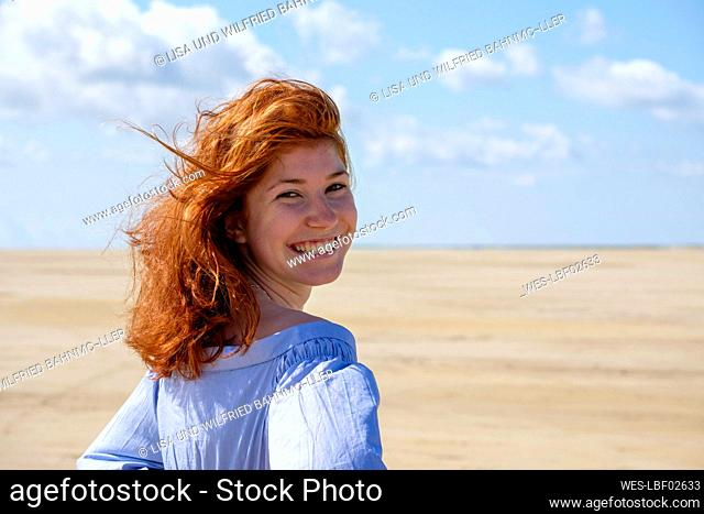 Smiling teenage girl looking over shoulder while standing at beach against sky on sunny day