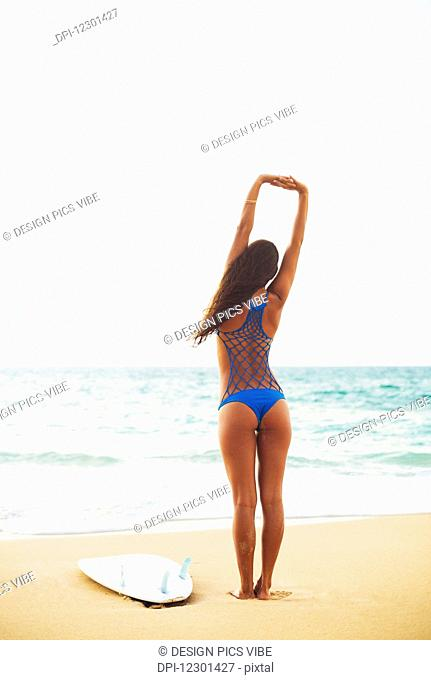 Beautiful Surfer Girl Stretching On The Beach. Summer Outdoor Lifestyle