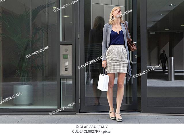 Woman leaving block of flats