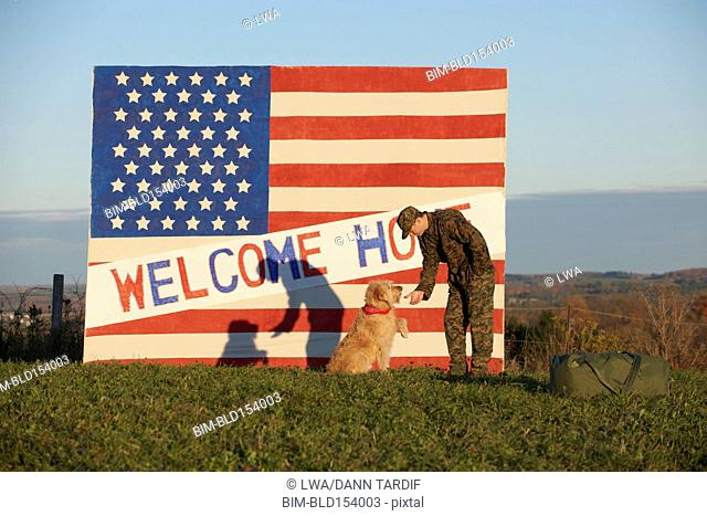 Returning Caucasian soldier greeting dog
