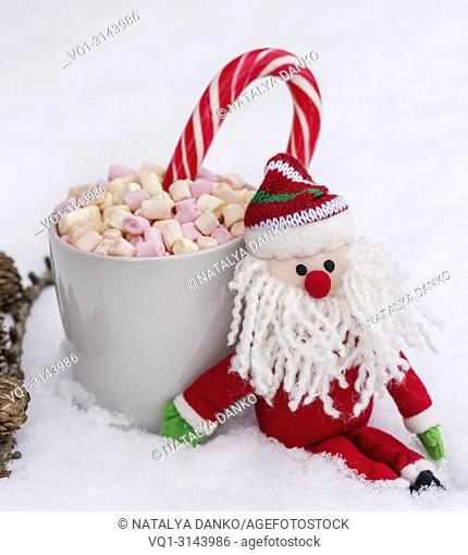 gray ceramic cup with hot chocolate, marshmallow and candy, near textile cute Santa Claus on white snow