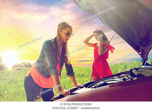 women with open hood of broken car at countryside