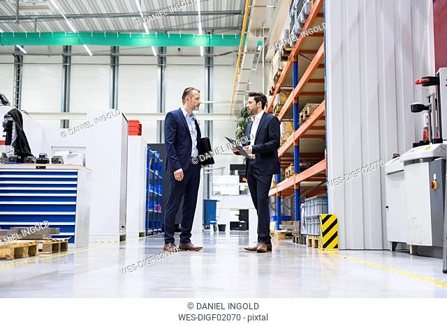 Two businessmen in factory shop floor