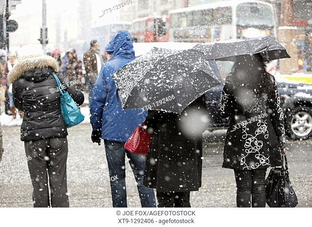 women standing at a pedestrian crossing on a cold snowy winters day Belfast Northern Ireland
