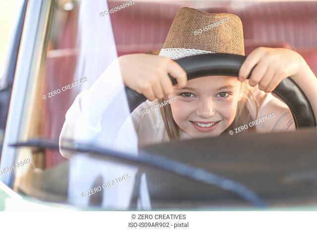 Young girl in driving seat of car, holding steering wheel, smiling