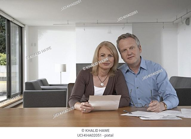 Middle-aged couple reading mail