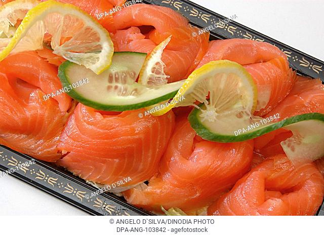 Non vegetarian Food , Fish Smoked Salmon (Rokt Lax in Swedish) surface texture clean and bone less , slices arranged in folded shapes and topped with lemon and...