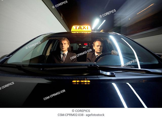 Taxi driver and passenger inside a cab, driving at high speed at night