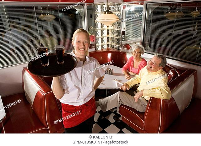 Portrait of waitress serving drinks to senior couple seated in old-fashioned diner, high angle view