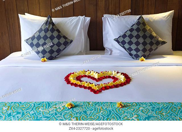 Hotel bed decorated with flowers petals, Ubud, Bali, Indonesia