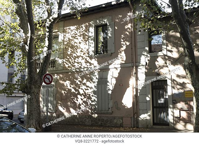 Plane trees cast dramatic shadows and reflections on a traditional pink and white shuttered house behind a residents only road sign in Avignon, Vaucluse