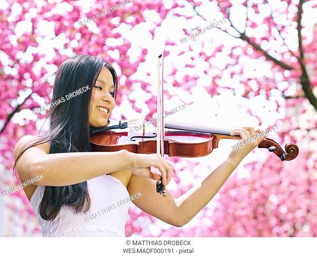 Female viola player in front of blossoming cherry tree