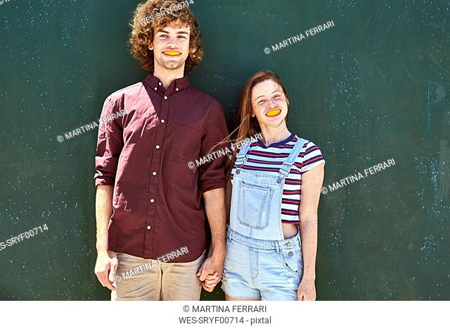 Young couple standing in front of a green wall with orange slices in their mouth