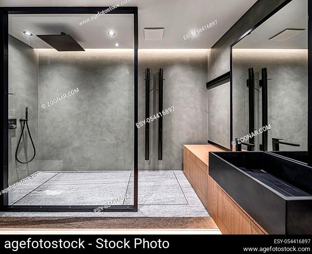 Bathroom in a modern style with gray tiled walls. There is a shower with a glass partition, wooden stand with a black sink and a faucet, large mirror