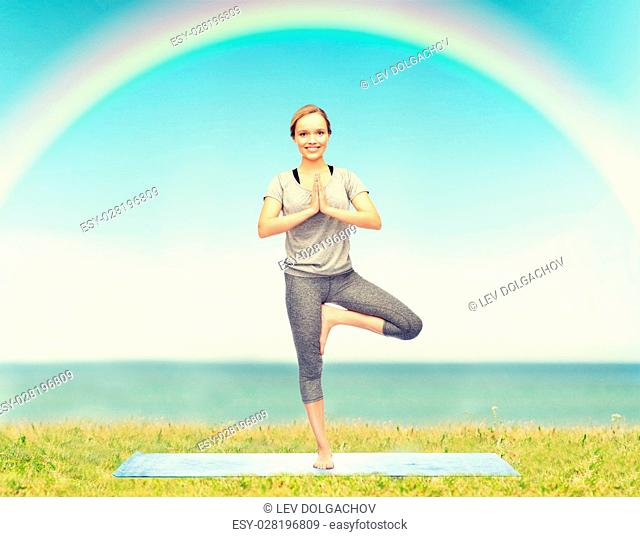 fitness, sport, people and healthy lifestyle concept - woman making yoga in tree pose on mat over blue sky, rainbow and sea background