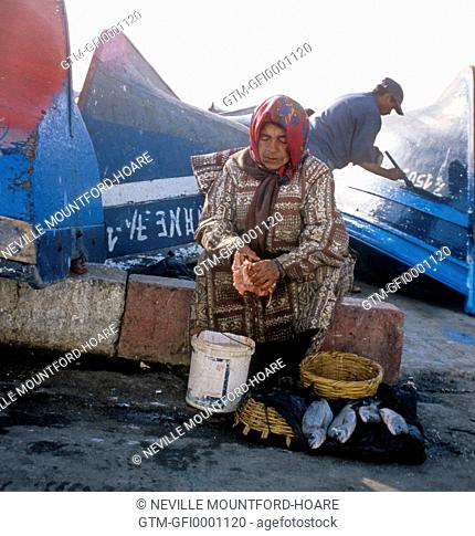 Old woman gutting fish over a bucket in a Moroccan harbour