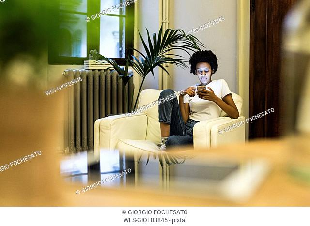 Young woman sitting in armchair, reading smartphone messages