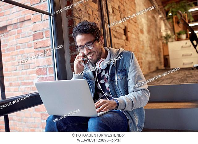 Young man with earphones and laptop sitting on office stairs, talking on the phone