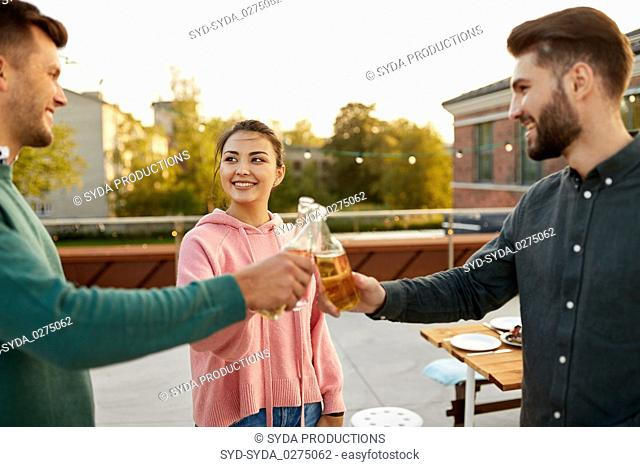 friends toast drinks at barbecue party on rooftop