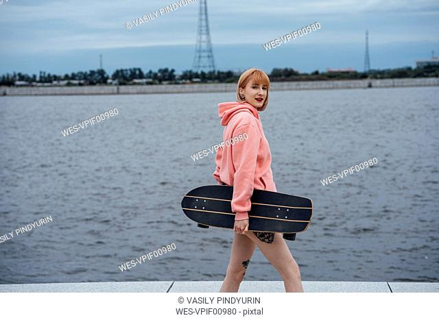 Young woman holding carver skateboard walking at the riverside