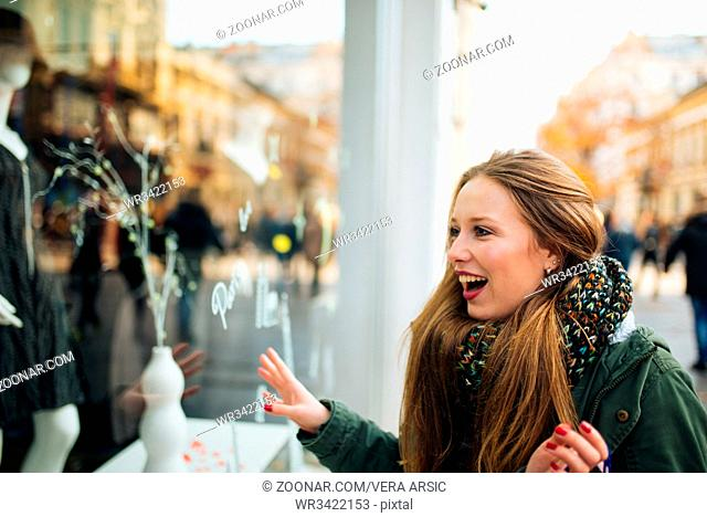 Attractive young long haired woman is excited in front of shopping window