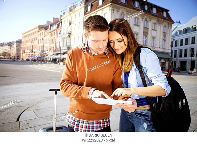 Mid adult couple on a city break using digital tablet