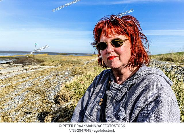 Krabbendijke The Netherlands - Woman sitting and enjoying the sun with the Oosterschelde in the background