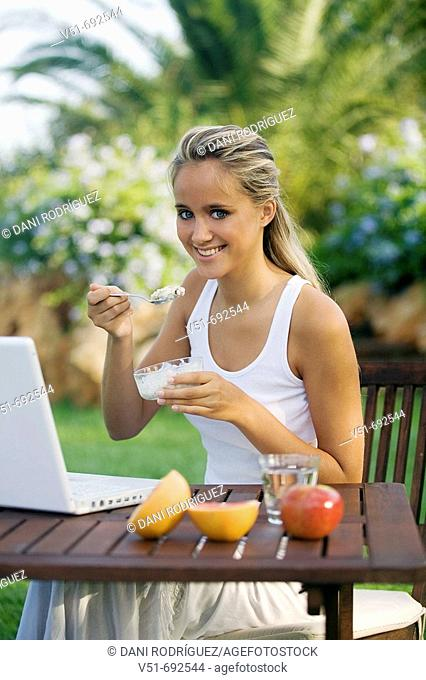 Young woman having breakfast and using laptop