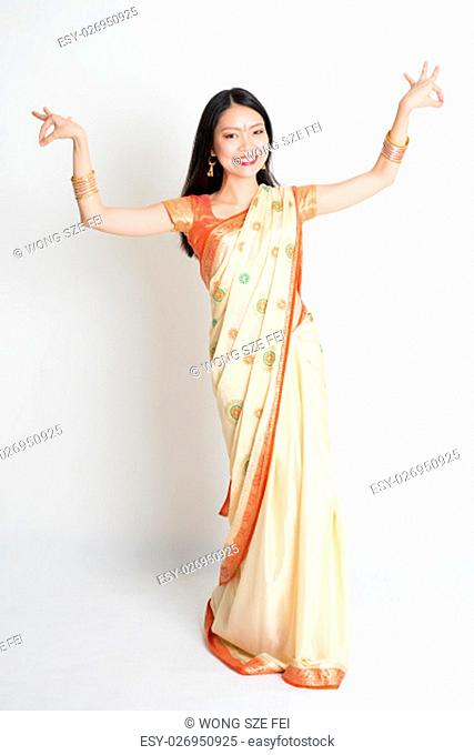 Portrait of young mixed race Indian Chinese female in traditional sari dress dancing, full length on plain background