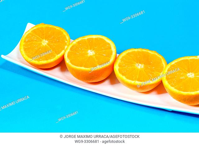 Oranges on a plate with blue background