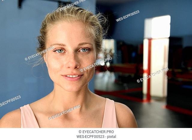 Portrait of smiling young blond woman in a gym